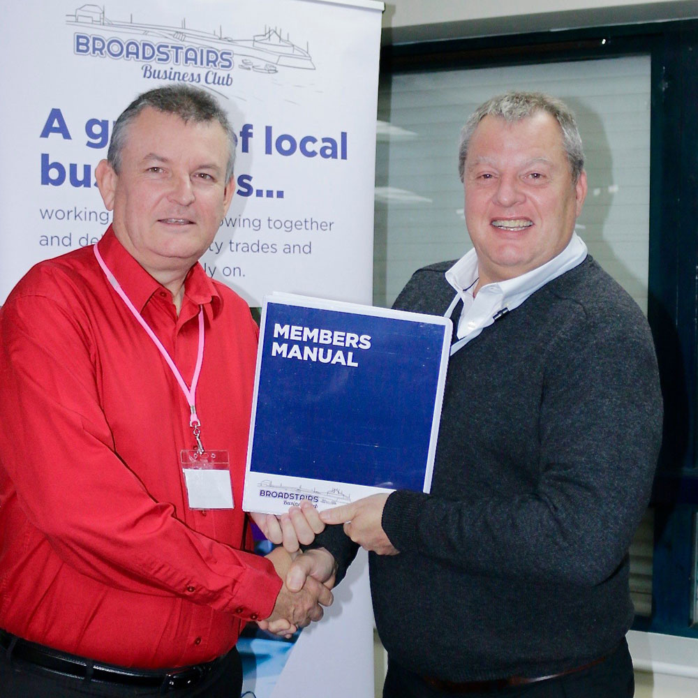 Photo of Hal Boddington, Utility Warehouse receiving his membership manual from chairman, Mike Chance